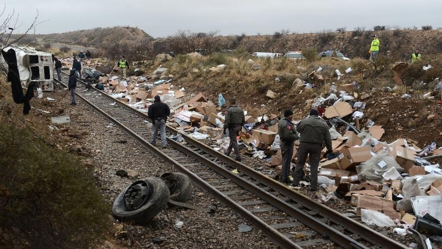 Debris is scattered along the train tracks as officials investigate a crash involving a Texas Department of Criminal Justice bus and a train Wednesday, Jan. 14, 2015 near Penwell, Texas. A bus carrying state prisoners skidded off an icy highway overpass, slid down an embankment and collided with a train. At least 10 people were killed in the crash, including eight prisoners and two guards, and four prisoners and another guard were injured, authorities said.  (AP Photo/Odessa American, Mark Sterkel)