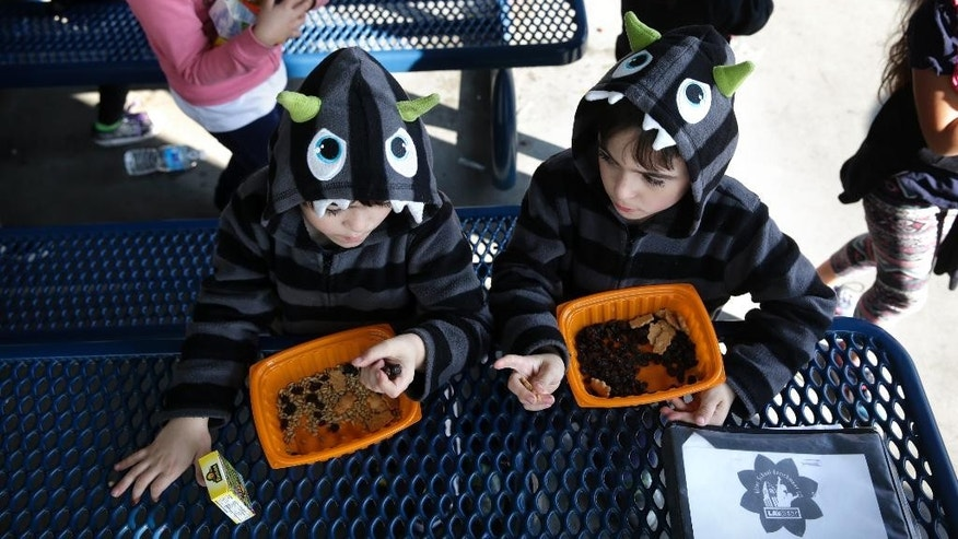 Kierian Eastaugh, 6, left, and his twin brother, Riley, eat their afternoon snack in the cafeteria area at Kingsley Elementary School, Tuesday, Jan. 13, 2015, in Los Angeles. Many of the students at the school in a low-income neighborhood of Los Angeles eat breakfast and lunch provided by the school. For the nearly 100 enrolled in the afterschool program, another meal is served: supper. The nation's second largest school district is doubling the number of students served dinner, with an eye toward eventually offering it at every school. (AP Photo/Jae C. Hong)