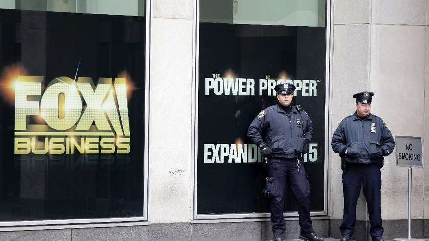 "New York City police officers stand guard outside the building that houses Rupert Murdoch's News Corp headquarters in Midtown Manhattan on Friday, Jan. 16, 2015. In the wake of the Paris terror attacks in early January, New York's Police Department is quietly expanding training for what it sees as the latest terror threat — teams of ""active shooters"" who arm themselves with high-powered rifles and open fire. (AP Photo/Mary Altaffer)"