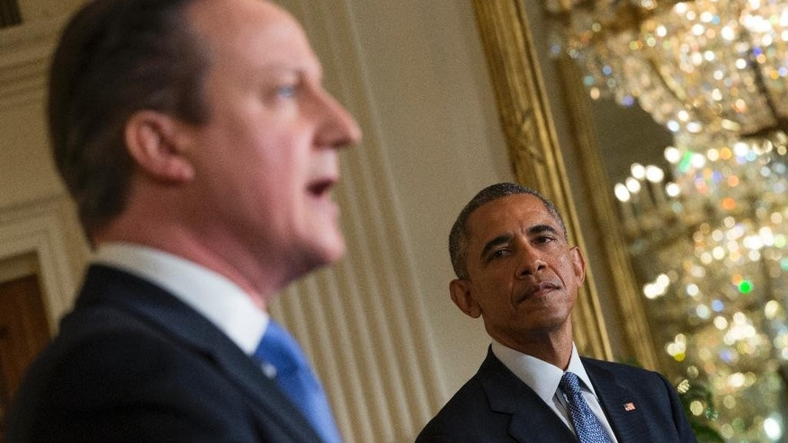 President Barack Obama listens as British Prime Minister David Cameron speaks during their joint news conference in the East Room of the White House in Washington, Friday, Jan. 16, 2015. In a show of trans-Atlantic unity, President Barack Obama and British Prime Minister David Cameron pledged a joint effort on Friday to fight domestic terrorism following deadly attacks in France. They also strongly urged the U.S. Congress to hold off on implementing new sanctions on Iran in the midst of nuclear talks. (AP Photo/Evan Vucci)