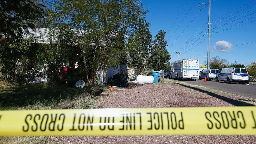 Phoenix Police tape surrounds the home of Brian Patrick Miller, 42, Wednesday, Jan. 14, 2015, in Phoenix. Miller was arrested on Tuesday as a suspect in the slaying of Angela Brosso and Melanie Bernas 20 years after the murders took place. (AP Photo/Ross D. Franklin)