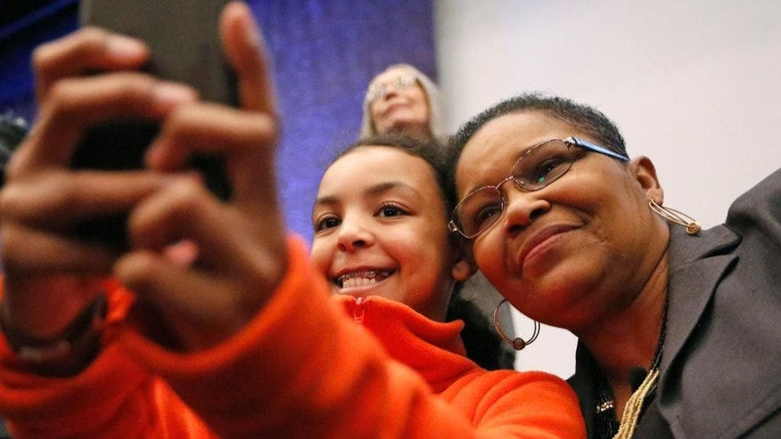 """Lynda Blackmon Lowery, right, poses for a photo with Olivia Ruiz, of the Calhoun School, during a pre-Martin Luther King Day appearance at the New York Historical Society, Sunday, Jan. 18, 2015, in New York. Blackmon, who spoke about her memoir """"Turning 15 on the Road to Freedom,"""" was the youngest person to join Martin Luther King Jr. for the nonviolent 1965 march from Selma to Montgomery, Alabama. (AP Photo/Kathy Willens)"""