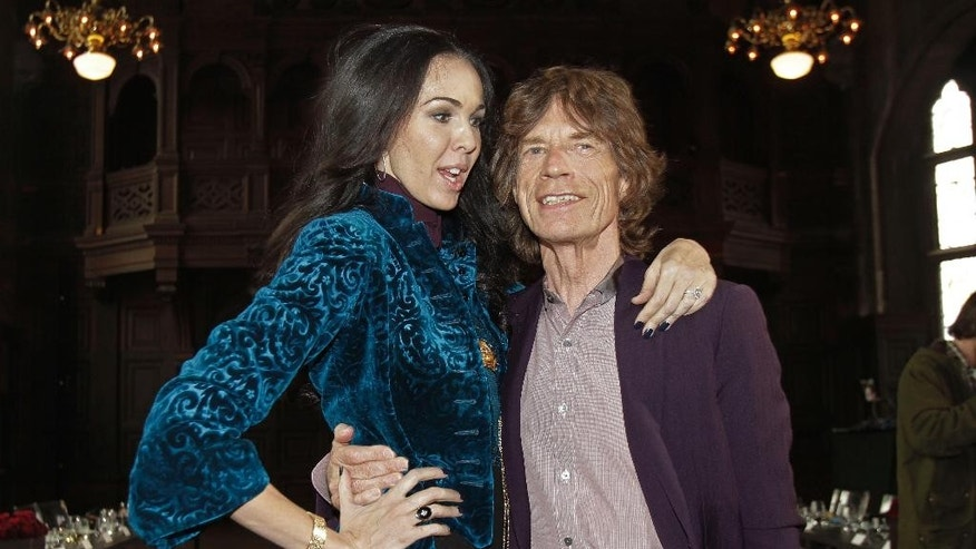 FILE - This Feb. 16, 2012 file photo shows singer Mick Jagger, right, with designer L'Wren Scott after her Fall 2012 collection was modeled during Fashion Week, in New York. Jagger has established a scholarship in honor of his late girlfriend, fashion designer Scott. The scholarship will allow one master's degree student per year over a period of three years to attend the elite Central Saint Martins, the London-based college announced this weekend. (AP Photo/Richard Drew, File)