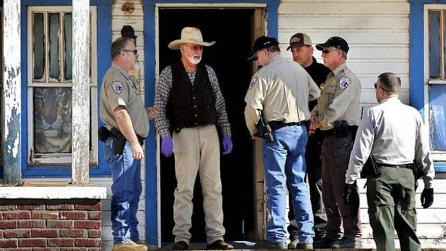 Agents from the Oklahoma State Bureau of Investigation and Washita County sheriff's deputies talk on the front porch of the house where Sentinel Police Chief Louis Ross was shot four times.(Courtesy: The Oklahoman)