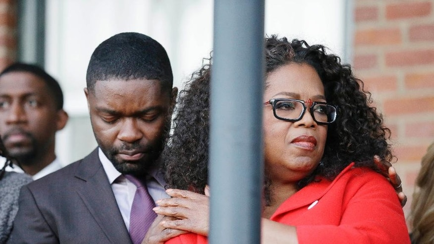 "Oprah Winfrey locks arms with David Oyelowo, who portrays Martin Luther King Jr. in the movie ""Selma"" as they pray just before they march to the Edmund Pettus Bridge in honor of Martin Luther King Jr., Sunday, Jan. 18, 2015, in Selma, Ala. (AP Photo/Brynn Anderson)"
