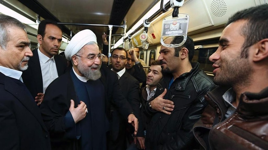 "In this photo released by the official website of the office of the Iranian Presidency, Iran's President Hassan Rouhani, center, talks with people while boarding a subway in Tehran, Iran, Monday, Jan. 19, 2015. Some Iranian top officials Monday went to work using subway and other public transportation systems showing their support for ""National Air Clean Day."" (AP Photo/Iranian Presidency Office, Mohammad Berno)"