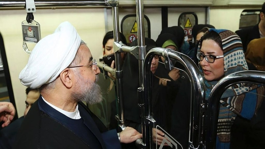 "In this photo released by the official website of the office of the Iranian Presidency, Iran's President Hassan Rouhani listens to a woman while boarding a subway in Tehran, Iran, Monday, Jan. 19, 2015. Some Iranian top officials Monday went to work using subway and other public transportation systems showing their support for ""National Air Clean Day."" (AP Photo/Iranian Presidency Office, Mohammad Berno)"