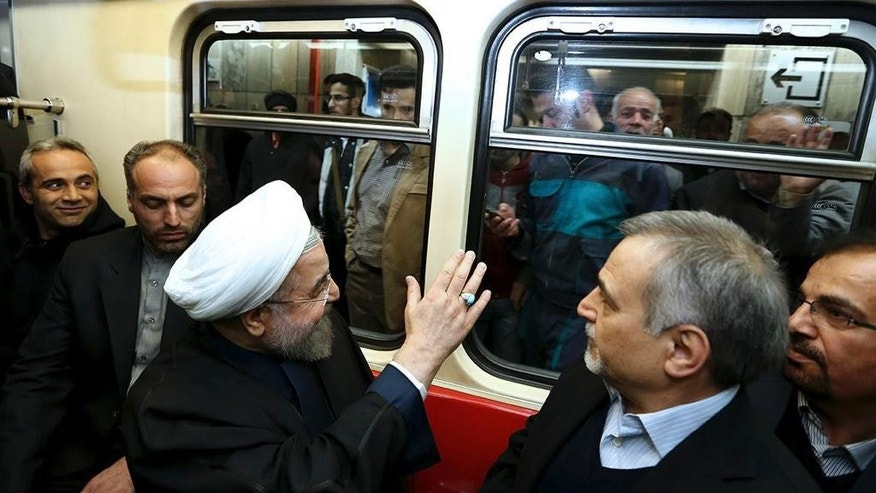 "In this photo released by the official website of the office of the Iranian Presidency, Iran's President Hassan Rouhani waves to people while boarding a subway train in Tehran, Iran, Monday, Jan. 19, 2015. Some Iranian top officials Monday went to work using subway and other public transportation systems showing their support for ""National Air Clean Day."" (AP Photo/Iranian Presidency Office, Mohammad Berno)"