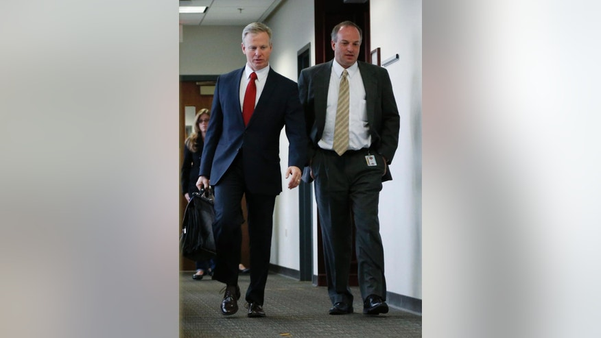 FILE - In this Dec. 8, 2014, file photo,  Arapahoe County, Colo. District Attorney George Brauchler, left, walks with an unidentified man out of courtroom after a pre-trial readiness hearing in Centennial, Colo., in the murder trial of James Holmes, who is charged with killing 12 moviegoers and wounding 70 more in a shooting spree in a crowded theatre in Aurora, Colo., in July 2012. The trial is set to start on Tuesday, Jan. 20, 2015. (AP Photo/David Zalubowski, File)