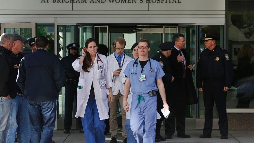 Medical personnel walk past law enforcement officials, right, as they depart the Shapiro building at Brigham and Women's Hospital, in Boston, Tuesday, Jan. 20, 2015. A person was critically shot at the hospital Tuesday and a suspect was in custody, Boston police said. (AP Photo/Steven Senne)