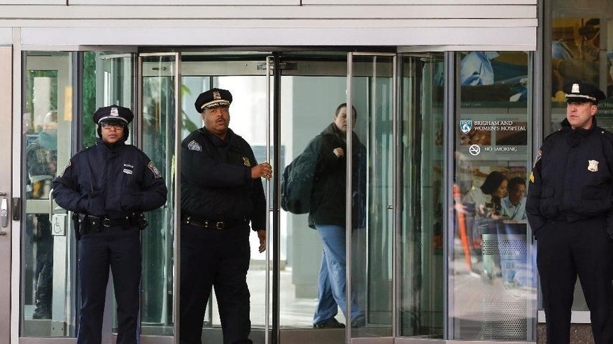 Boston Police Superintendent-in-Chief William Gross, center left, walks through a revolving door as he departs the Shapiro building at Brigham and Women's Hospital, Tuesday, Jan. 20, 2015 in Boston. A person was critically shot at the hospital Tuesday and a suspect was in custody, Boston police said. (AP Photo/Steven Senne)
