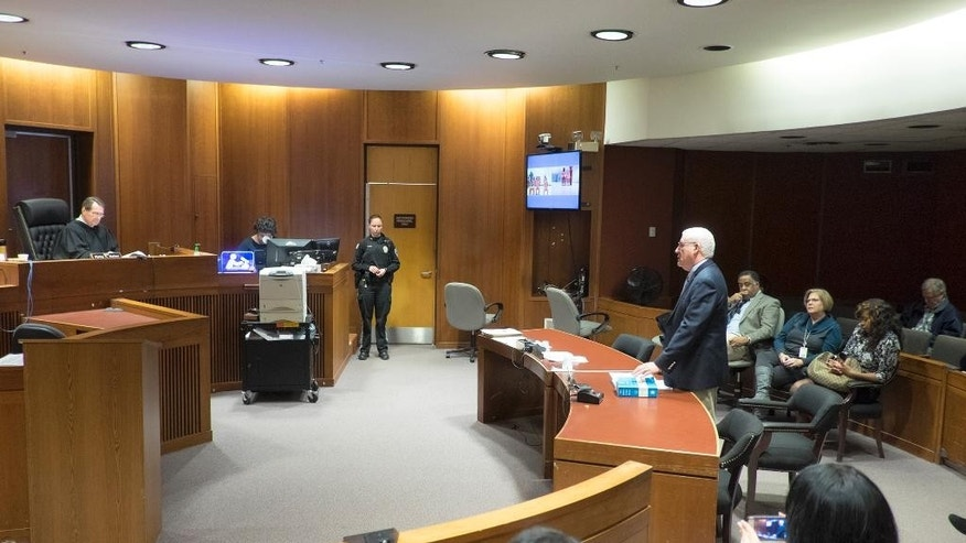 Judge Philip E. Haines, left, addresses Hyphernkemberly Dorvillier via teleconference during her initial court appearance at the Burlington County N.J. Courthouse in Mount Holly, N.J., Tuesday, Jan. 20, 2015. Dorvillier is accused of killing her newborn baby by immolation. The judge maintained her $500,000 bail, which was set after police found the baby in flames Jan. 16 in the middle of a residential road. First Assistant Prosecuter James Ronca, right listens. (AP Photo/The Philadelphia Inquirer, Ed Hille, Pool)