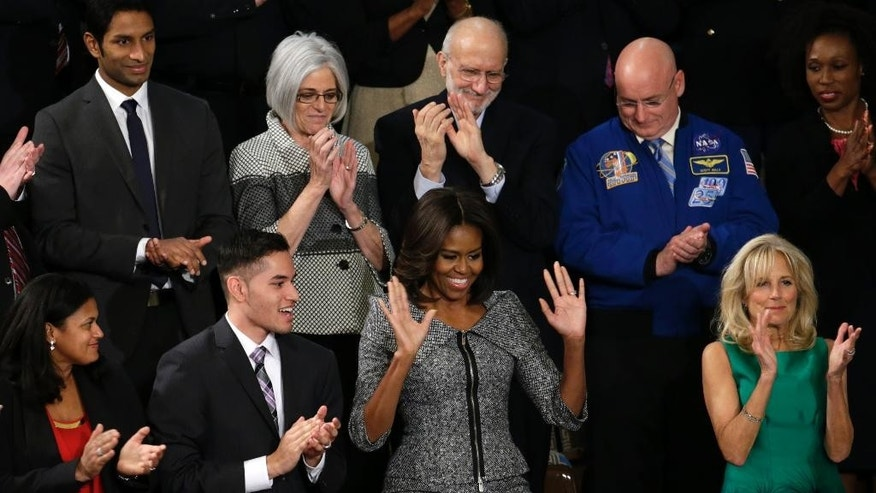 First lady Michelle Obama acknowledges applause on  Capitol Hill in Washington, Tuesday, Jan. 20, 2015, before President Barack Obama's State of the Union address before a joint session of Congress. Front rowm from left are, Astrid Muhammad, Anthony Mendez, Mrs. Obama, and Jill Biden. Second row, from left are, Pranav Shetty, Judy Gross, Alan Gross and Scott Kelly.   (AP Photo/Pablo Martinez Monsivais)