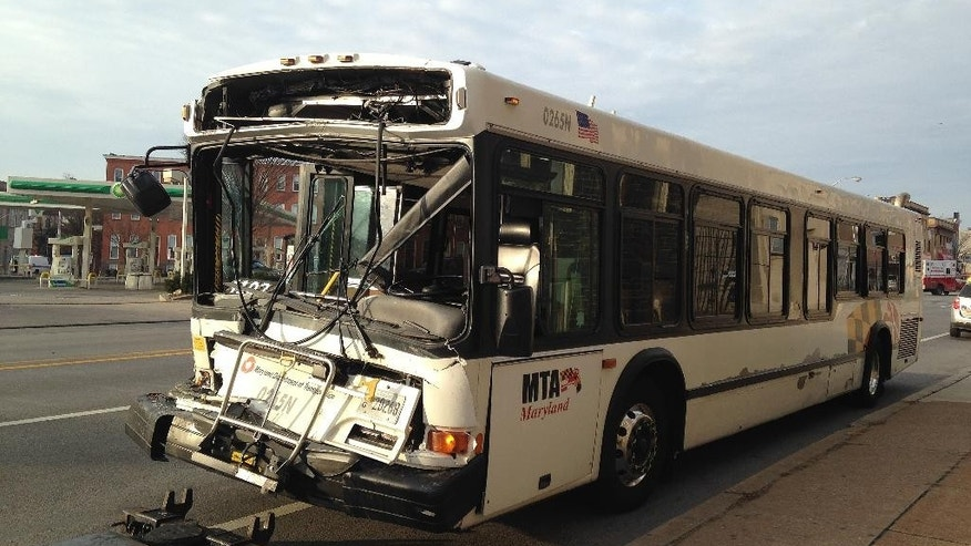 A tow truck prepares to remove a Maryland Transit Administration bus on Wednesday, Jan. 21, 2015, in Baltimore from the scene of its collision with a smaller transit administration bus for disabled riders. Passengers on the larger bus were injured; the disability service bus carried only the driver. (AP Photo/Juliet Linderman)