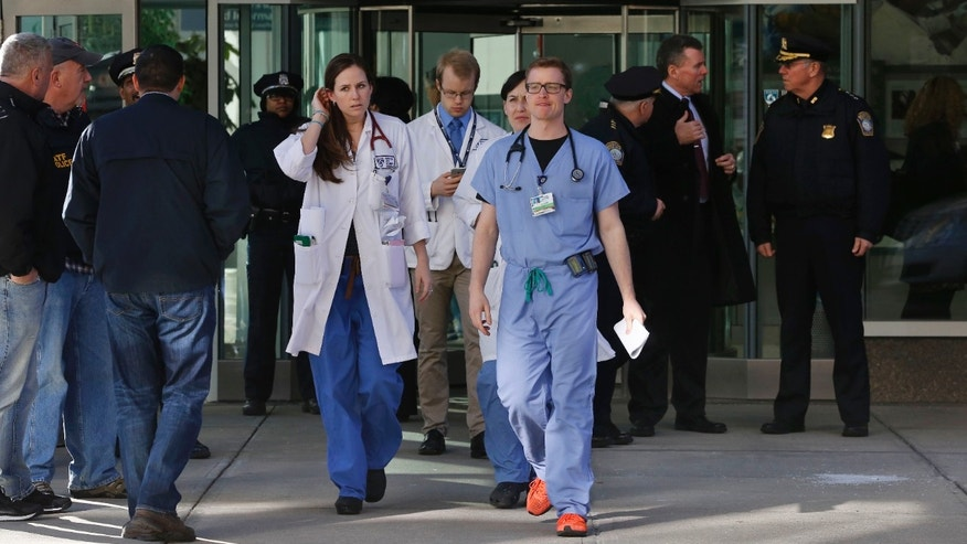 Jan. 20, 2015: Medical personnel walk past law enforcement officials, right, as they depart the Shapiro building at Brigham and Women's Hospital, in Boston.