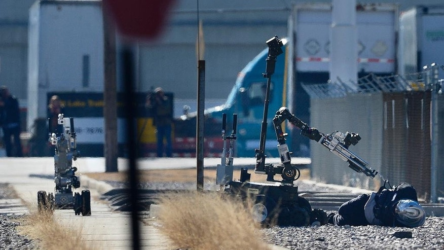 A bank robbery suspect wearing a motorcycle helmet lies handcuffed on the ground as a bomb squad robot searches his vest, Thursday, Jan. 22, 2015, in Salt Lake City. According to authorities, officers were struggling with the man as they tried to arrest him on suspicion of robbing a nearby bank when they noticed he was wearing a vest with wires. (AP Photo/The Salt Lake Tribune, Scott Sommerdorf)