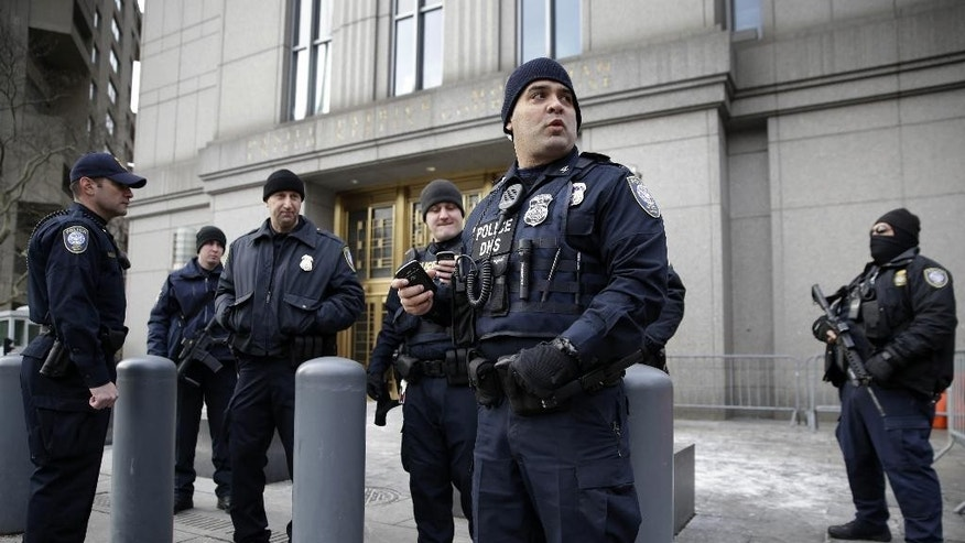 Security watch over the entrance to a federal courthouse in New York, Thursday, Jan. 22, 2015.  Opening statements are expected to begin Thursday after jury selection is completed in the trial of a man charged with conspiring in the 1998 bombings of two U.S. embassies in Africa. The attacks killed 224 people, including a dozen Americans. (AP Photo/Seth Wenig)