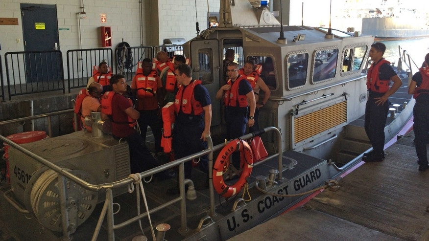 Jan. 22, 2015: Coast Guard crew members standing with 11 survivors of the Tug Nalani at Coast Guard Station Honolulu.