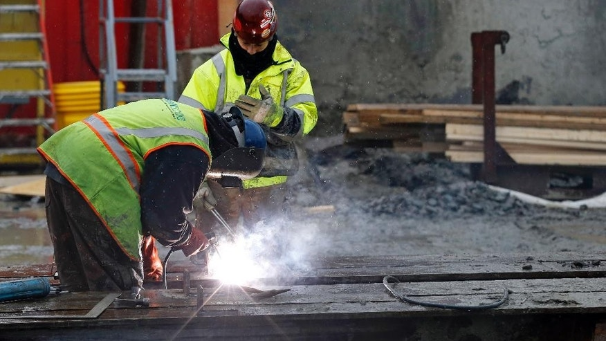 In this Monday, Jan. 12, 2015 photo, workers weld at a commercial construction site in Boston. The Conference Board releases its index of leading indicators for December on Friday, Jan. 23, 2015. (AP Photo/Elise Amendola)