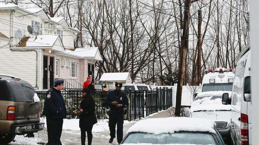 Police gather near a home located at 231-11 148th Avenue, left, Saturday, Jan. 24, 2015, in the Queens borough of New York.  Police say a father shot his daughters, his girlfriend and her mother in their home and then killed himself after the shooting that left three generations of women dead and a 12-year-old critically injured. New York Police Department spokesman Steve Davis says Jonathon Walker's body was found in a car, with a gun inside, in an isolated part of Queens after Saturday's pre-dawn shootings. (AP Photo/Frank Franklin II)