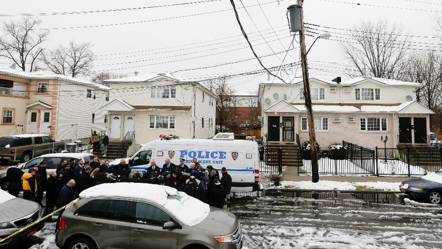 Media gather near 231-11 148th Avenue during a news conference Saturday, Jan. 24, 2015, in the Queens borough of New York.  Police say a father shot his daughters, his girlfriend and her mother in their home and then killed himself after the shooting that left three generations of women dead and a 12-year-old critically injured. New York Police Department spokesman Steve Davis says Jonathon Walker's body was found in a car, with a gun inside, in an isolated part of Queens after Saturday's pre-dawn shootings.  (AP Photo/Frank Franklin II)