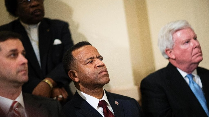 FILE- In this Jan. 13, 2015 file photo, Former Atlanta fire chief Kelvin Cochran, second from left, listens during a rally by religious groups supporting Cochran following his termination, Tuesday, Jan. 13, 2015, in Atlanta. Even as the U.S. Supreme Court gets ready to decide whether gay couples can marry, lawmakers in the South and West are doubling down on the culture wars, backing longshot legislation targeting gay rights. In Georgia, the debate flared this month when Atlanta Mayor Kasim Reed fired the city's fire chief after learning the chief self-published a book describing homosexuality as a perversion. Reed, a Democrat, said Cochran never got city permission to publish the book, but Cochran said he did. (AP Photo/David Goldman)