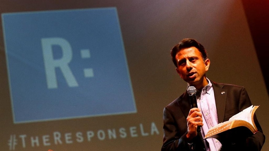 Louisiana Gov. Bobby Jindal reads from the bible during a prayer rally, Saturday, Jan. 24, 2015, in Baton Rouge, La. Jindal continued to court Christian conservatives for a possible presidential campaign with a headlining appearance at an all-day prayer rally hosted by the American Family Association. (AP Photo/Jonathan Bachman)