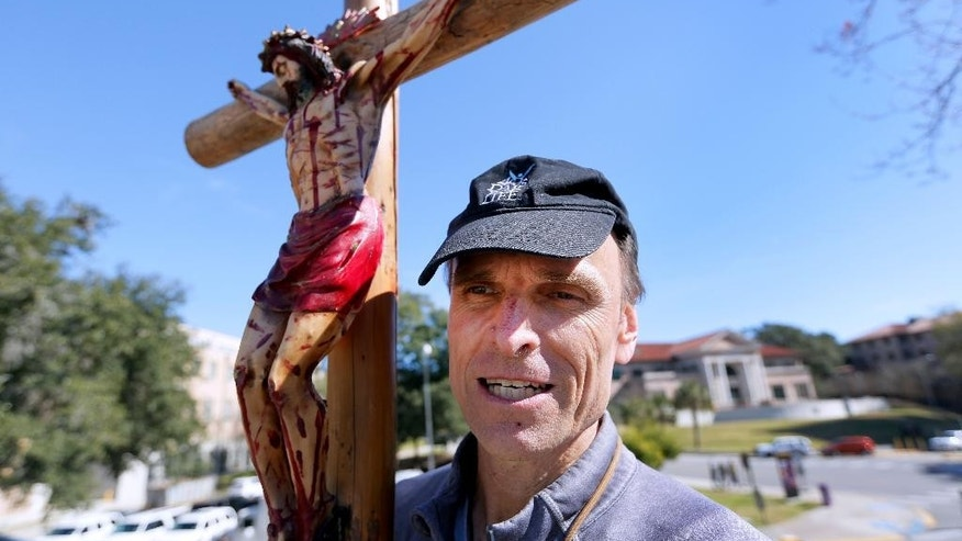 Richard Mahoney, holds a crucifix outside of an all-day prayer rally headlined by Gov. Bobby Jindal, Saturday, Jan. 24, 2015, in Baton Rouge, La. Jindal continued to court Christian conservatives for a possible presidential campaign with a headlining appearance at an all-day prayer rally hosted by the American Family Association. (AP Photo/Jonathan Bachman)