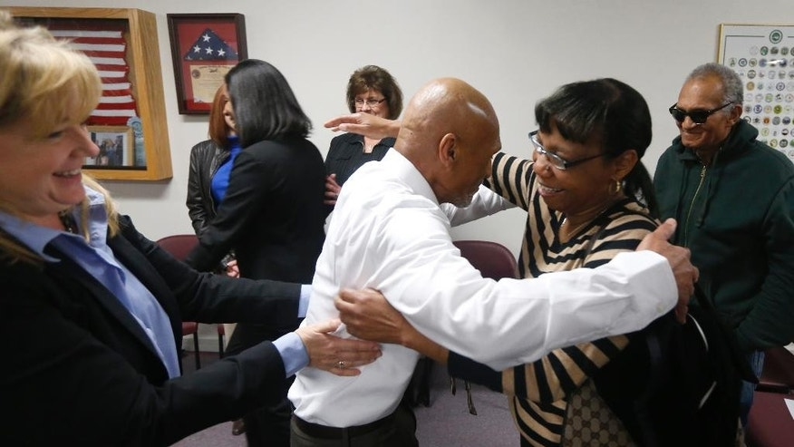 Joseph Sledge hugs his sister Barbara Kinlaw after a special session of superior court in Whiteville, N.C. on Friday, Jan. 23,  2015. Sledge, 70, was freed from prison Friday, after a panel of judges found that he was wrongly convicted in the stabbing deaths of a mother and daughter nearly four decades ago. Christine Mumma, director of the North Carolina Center on Actual Innocence, is to the left. (AP Photo/The News & Observer, Ethan Hyman)