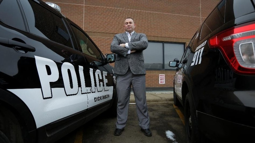 "In this Thursday, Dec. 18, 2014 photo, Dickinson Police Chief Dustin Dassinger stands next to patrol vehicles in Dickinson, N.D. ""Some of the North Dakota niceness has left our community,"" says Dassinger. ""It's an adjustment, not just for law enforcement but for everyone."" A highly visible four-person team patrols the bars on random Friday and Saturday nights to head off brawls that have become increasingly common. Police reported calls were up nearly 45 percent from 2009 to 2014, when there were more than 27,000. (AP Photo/Eric Gay)"