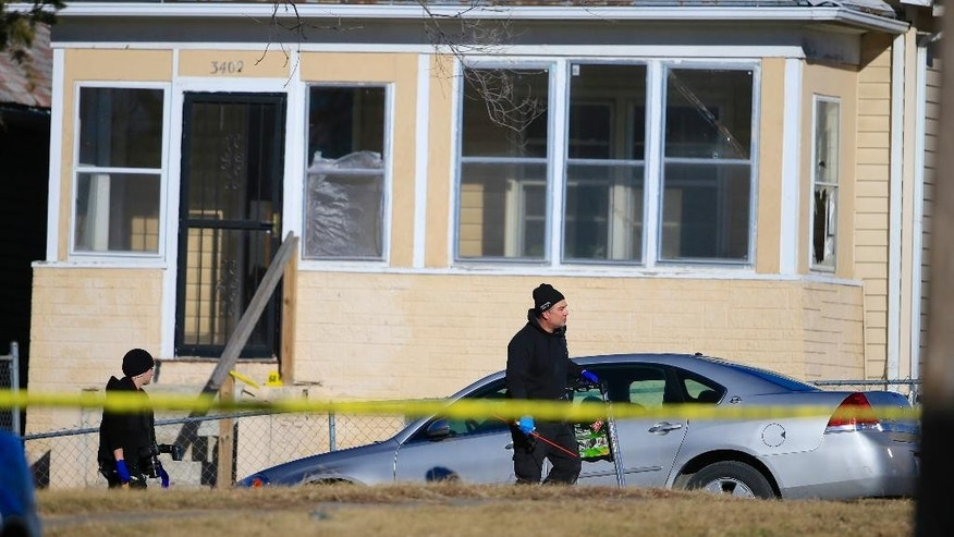 A crime lab investigators walk past a house where a shooting in Omaha, Neb., Saturday, Jan. 24, 2015.  Two women were shot to death and six people were wounded early Saturday at a house party in Omaha. (AP Photo/Nati Harnik)
