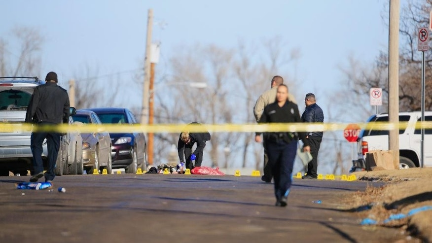Crime lab investigator and police officers work the scene of a shooting in Omaha, Neb., Saturday, Jan. 24, 2015.  Two women were shot to death and six people were wounded early Saturday at a house party in Omaha. (AP Photo/Nati Harnik)