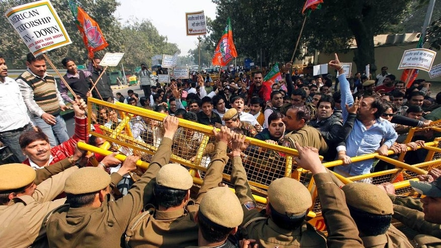FILE - In this Feb. 4, 2011 file photo, activists of India's main opposition Bharatiya Janata Party (BJP) youth wing break police barricades at a protest  in New Delhi, India, against alleged radio collars placed on Indian students of the Tri-Valley University in California. Several Indian students of the U.S. university, shut down on charges of a massive immigration fraud, were forced to wear radio collars around their ankles so that the U.S. authorities could keep a tab on their movements. Investigators say Tri-Valley was among the largest school fraud scams they encountered, involving hundreds of mostly Indian nationals living in cities as far away from Pleasanton as Miami, Chicago and Honolulu. (AP Photo/Mustafa Quraishi, File)