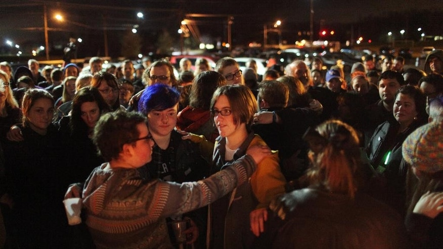 "This Saturday, Jan. 3, 2015 photo shows a large crowd participating in a group hug at the end of a candle light vigil to remember the life of Leelah Alcorn, a 17 year-old transgender girl who committed suicide, in Kings Mills, Ohio. In what's believed to be her final message, Alcorn implored: ""My death needs to mean something."" It has, at least making her a poignant new face for the transgender movement and those struggling to fit in. (AP Photo/The Enquirer, Meg Vogel)"