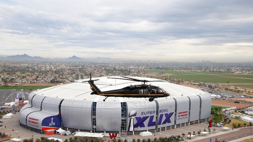 A U.S. Customs and Border Protection Black Hawk helicopter flies above University of Phoenix Stadium, site of the NFL Super Bowl XLIX football game, for a security demonstration for the media Monday, Jan. 26, 2015, in Glendale, Ariz. The Black Hawk helicopters and truck-sized X-ray machines have been brought to the Super Bowl venue to assist with the security effort. (AP Photo/Ross D. Franklin)