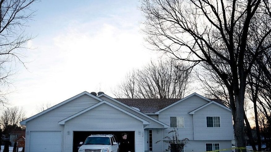 "In this Sunday, Jan. 25, 2015, photo, a police officer stands in front of a home in Eagan, Minn. A 15-year-old boy unintentionally fatally shot his 13-year-old brother while playing ""cops and robbers"" after the boys discovered their father's hidden gun. (AP Photo/Star Tribune, Carlos Gonzalez) MANDATORY CREDIT"