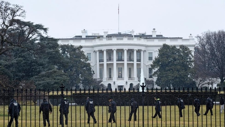 Secret Service officers search the south grounds of the White House in Washington, Monday, Jan. 26, 2015. A device, possibly an unmanned aerial drone, was found on the White House grounds during the middle of the night while President Barack Obama and the first lady were in India, but his spokesman said Monday that it posed no threat. (AP Photo/Susan Walsh)