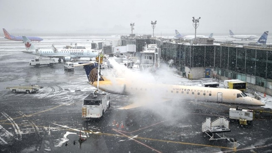 Jan. 26, 2015: A plane is de-iced at LaGuardia Airport in New York. Airlines canceled thousands of flights into and out of East Coast airports as a major snowstorm packing up to 3 feet of snow barrels down on the region. (AP Photo/Seth Wenig)