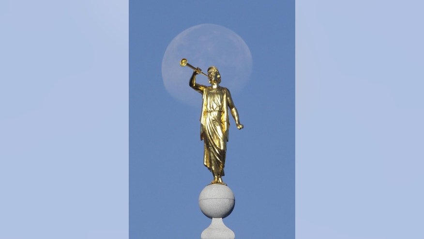 "FILE- In this Sept. 11, 2014, file photo, the angel Moroni statue sits atop the Salt Lake Temple in Temple Square as the moon sets in Salt Lake City. Mormon church leaders are making a national appeal for a ""balanced approach"" in the clash between gay rights and religious freedom. The church is promising to support some housing and job protections for gays and lesbians in exchange for legal protections for believers who object to the behavior of others. (AP Photo/Rick Bowmer, File)"