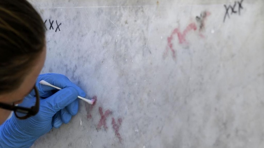 Emily Ford, a restoration consultant for the organization Save Our Cemeteries, works to remove graffiti from the tomb of Marie Laveau inside St. Louis Cemetery No. 1 in New Orleans, Tuesday, Jan. 27, 2015. The historic New Orleans cemetery that may have started the city's tradition of above-ground crypts will soon be off-limits to tourists on their own because of repeated vandalism among the tombs, the Roman Catholic archdiocese that owns the property has announced. Starting in March, entry to St. Louis Cemetery No. 1 and its labyrinth of mausoleums will be restricted to the relatives of the dead buried there and to tourists whose guide is registered with the Archdiocese of New Orleans. (AP Photo/Gerald Herbert)
