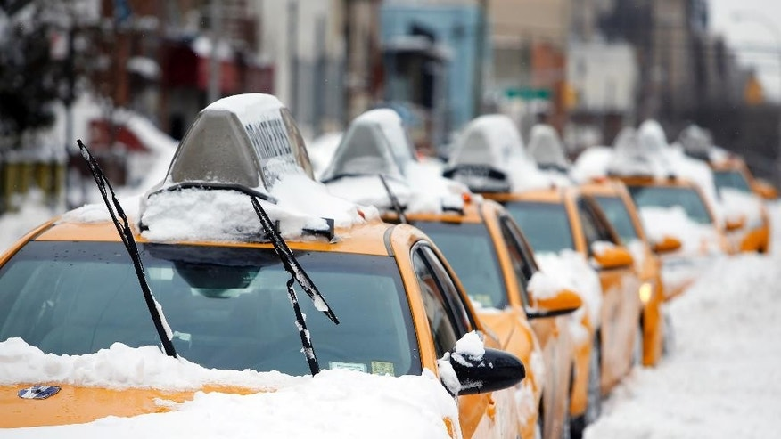 Taxis that belong to Arthur Cab Leasing Corp.,  stand idle outside the company's lot before being put it back into service following a winter storm, Tuesday, Jan. 27, 2015, in the Queens borough of New York.  Manager Shaon Chowdhury estimates that the winter storm has cost his company approximately $60,000 in lost revenue and added expenses. (AP Photo/Jason DeCrow)