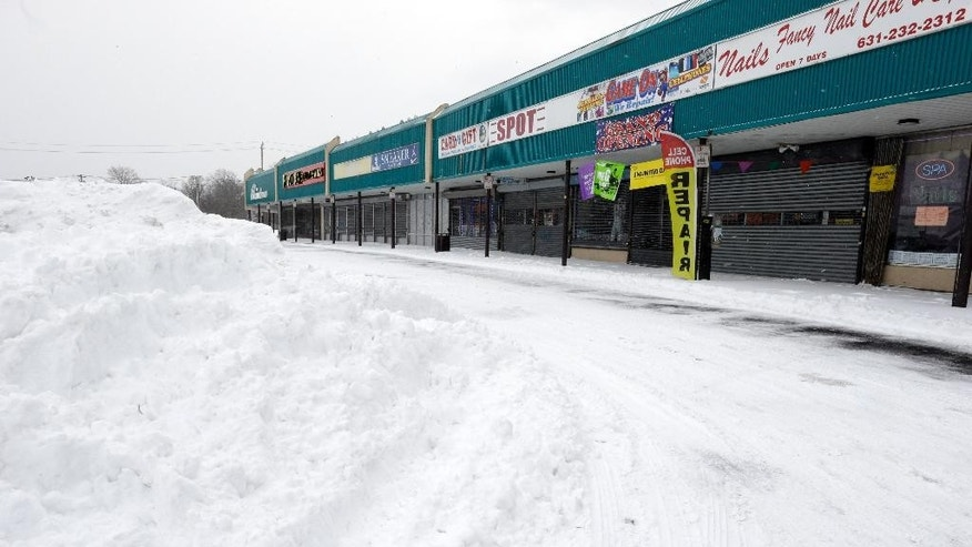 Stores are closed at a Central Islip, N.Y. strip mall, Tuesday, Jan. 27, 2015.  A storm packing blizzard conditions spun up the East Coast early Tuesday, pounding coastal eastern Long Island into Maine with high winds and heavy snow. (AP Photo/Mary Altaffer)