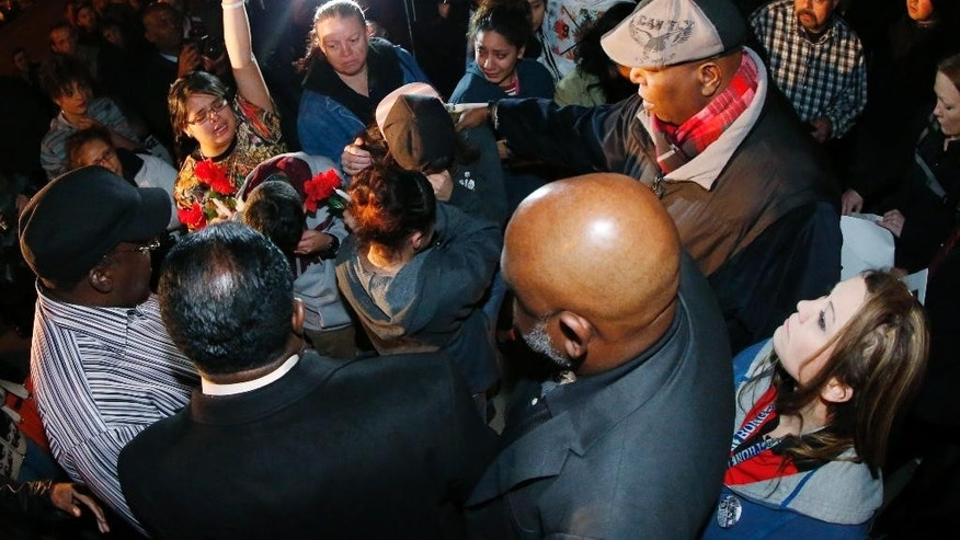 Cynthia Valdez raises her arm at left while Rev. Terrence Hughes, right in hat, leads people in prayer during a vigil near the scene of the early morning fatal shooting of a young woman who hit and injured a Denver Police Department officer while driving a stolen vehicle Monday, Jan. 26, 2015, in northeast Denver. Valdez said that she was a friend of the woman who was shot by police in the incident. (AP Photo/David Zalubowski)