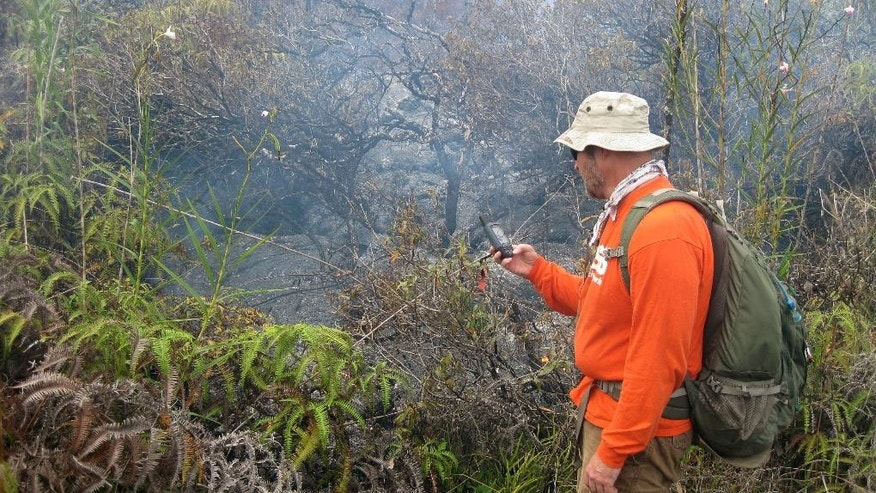In this Jan. 26, 2015 photo released by the U.S. Geological Survey a geologist taking a GPS waypoint of the leading edge of the lava flow near the town of Pahoa on the Big Island of Hawaii. The public has a few days left to get a glimpse of Hawaii lava from a viewing area set up by the county. After slow-moving lava poured into the Pahoa trash transfer station, it was turned into a public viewing area last month. (AP Photo/U.S. Geological Survey)