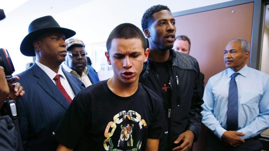 Jose Castaneda, front, who lost his cousin in a Denver Police shooting early Monday, is led away by activist Anthony Grimes from a meeting Tuesday, Jan. 27, 2015, with officials from the office of the Denver District Attorney. Activists are calling for a special prosecutor to invesitage the fatal shooting of the young woman who allegedly hit and injured a Denver Police Department officer while driving a stolen vehicle early Monday in a northeast Denver alleyway. (AP Photo/David Zalubowski)