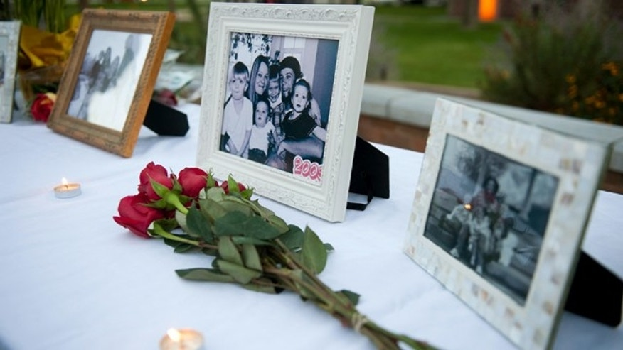 FILE - In this Oct. 2, 2014 file photo, flowers and photos are on display during a vigil for the Strack family at Pioneer Park in Provo, Utah. (AP Photo/The Daily Herald, Grant Hindsley, File) MANDATORY CREDIT