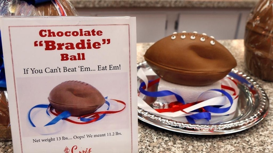 "A ""deflated"" chocolate football called a ""Bradie"" Ball is on display at Sarris Candy store in in Canonsburg, Pa., on Wednesday, Jan. 28, 2015. Owner Bill Sarris says they came up with the idea to poke fun at the controversy surrounding under-inflated footballs on Tuesday.  The display item isn't for sale.  (AP Photo/Keith Srakocic))"