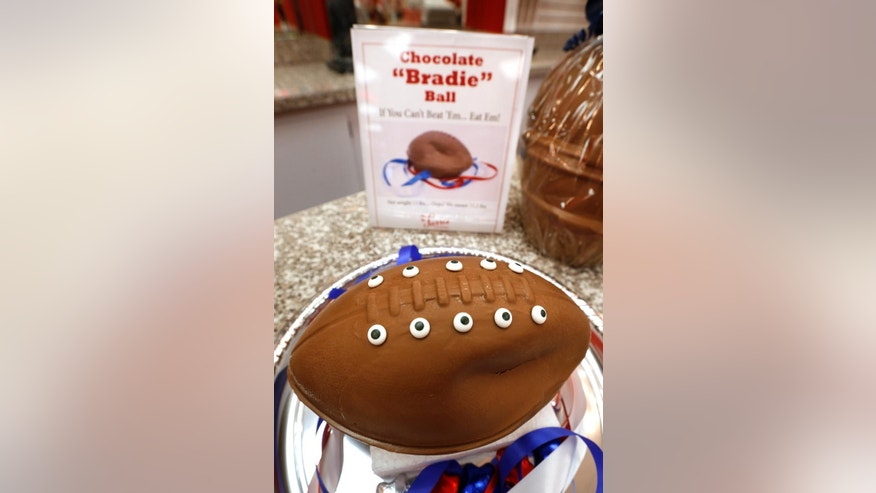 "A ""deflated"" chocolate football called a ""Bradie"" Ball is on display at Sarris Candy store in in Canonsburg, Pa., on Wednesday, Jan. 28, 2015. Owner Bill Sarris says they came up with the idea to poke fun at the controversy surrounding under-inflated footballs on Tuesday.  The display item isn't for sale.  (AP Photo/Keith Srakocic)"