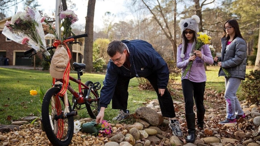 "Jason Hoffman, left, places flowers at a makeshift memorial with his daughters Jaycee, 9, center, and Nolene, 11, outside the home of 69-year-old Elrey ""Bud"" Runion and his 66-year-old wife, June, Tuesday, Jan. 27, 2015, in Marietta, Ga. Authorities have positively identified two bodies as those of the Runions, who disappeared after driving three hours away to buy a classic auto, and the suspect already in custody has been charged with murder and armed robbery. (AP Photo/David Goldman)"