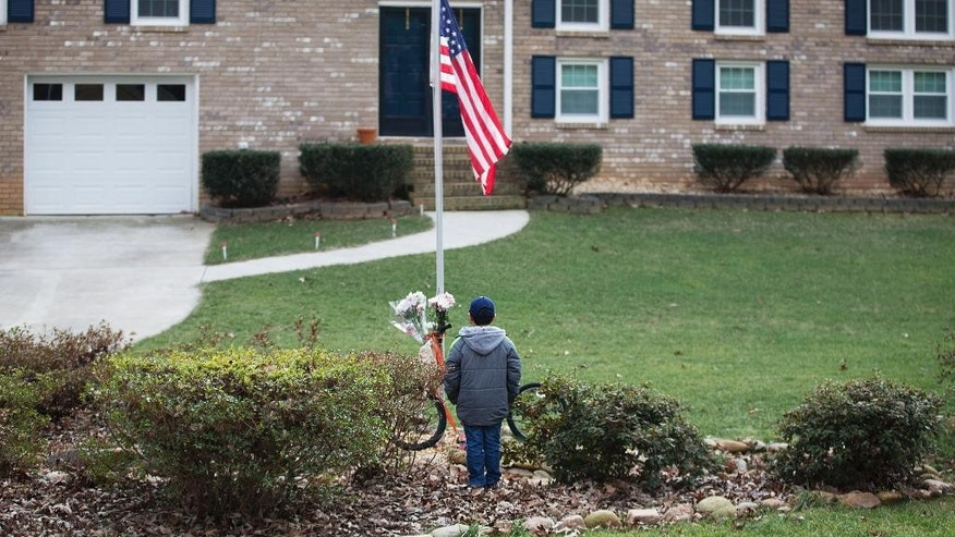 "Matthew Franden, 10, stands at a makeshift memorial outside the home of his neighbors Elrey ""Bud"" Runion and his 66-year-old wife, June, as an American flag flies at half-staff, Tuesday, Jan. 27, 2015, in Marietta, Ga. Authorities have positively identified two bodies as those of the Runions, who disappeared after driving three hours away to buy a classic auto, and the suspect already in custody has been charged with murder and armed robbery. (AP Photo/David Goldman)"